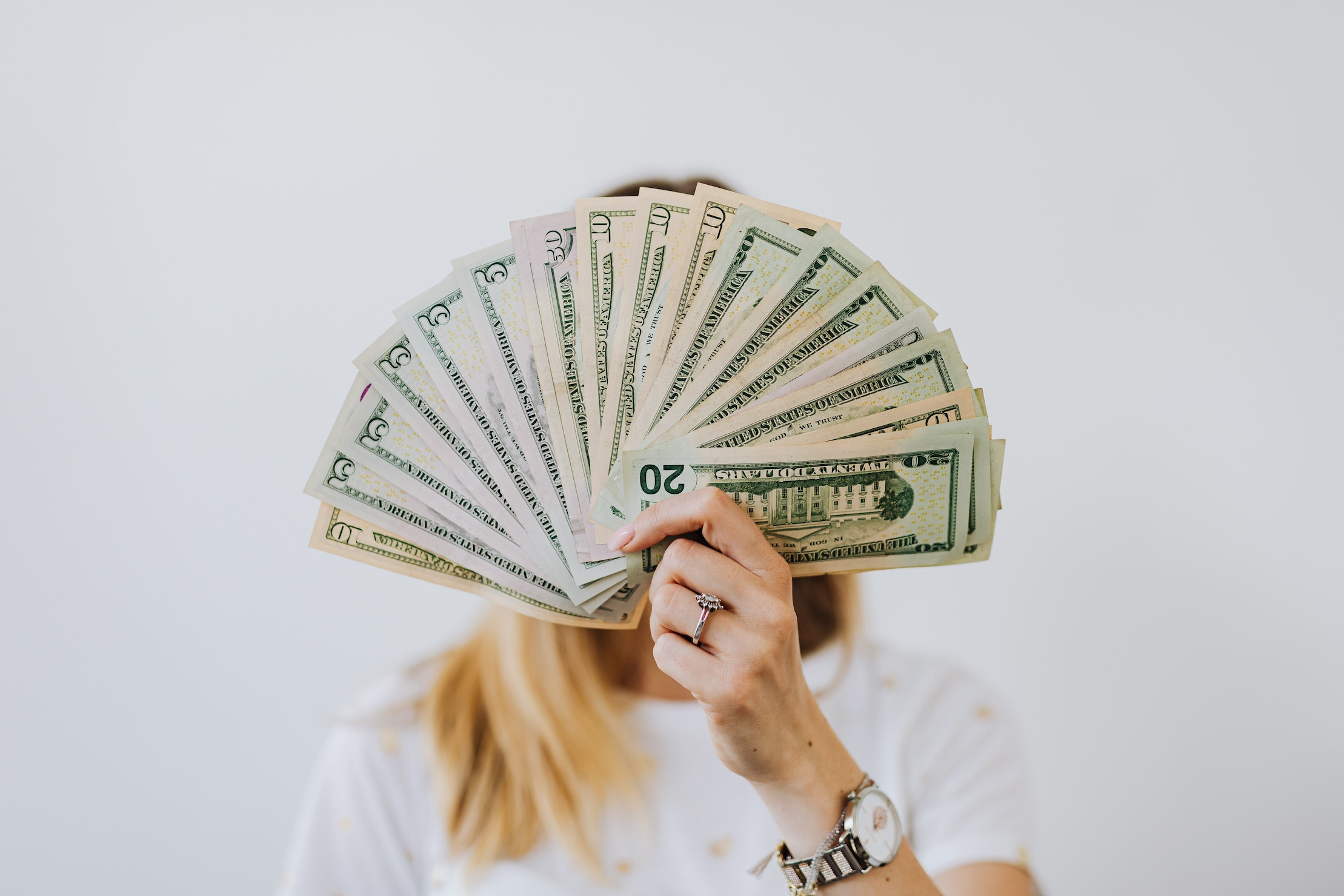 woman with money in front of face showing an increase your profits